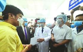 大水鑊醫院院長阮知識醫生向病人李子超(黃衣)遞交出院證。