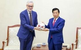 文體與旅遊部長阮玉善(右)向德國駐越南特命全權大使吉多‧希爾德納贈送紀念品。(圖源:明慶)