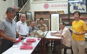 李克柔(左一),張路(左二),黃獻平 (左三),李松年(右二)在市各民族文學藝術會址為聯展準備工作。