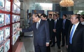 政府總理阮春福觀看電台的圖片展。(圖源:越通社)