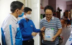 青年向人民贈送消毒洗手液。