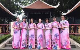 第十一郡婦聯會的越、華婦女穿著長衫拍照。