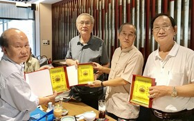 黃有義理事長(右二)向各書畫家贈送紀念章。