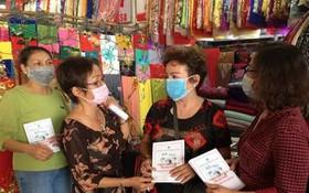 華人商販應氏蓮(左二)派發防疫手冊給商販。
