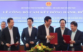 新聞與傳播部長阮孟雄(左三)和教育與培訓部長馮春迓(右二)出席見證兩部各職能部門之間的簽署儀式。(圖源:大光)