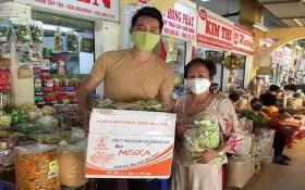 華人商販應氏蓮將防疫用品 交給阮飛雄歌星。