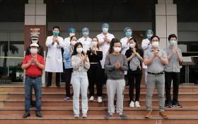 在中央熱帶病醫院收治的11 名新冠肺炎患者痊愈出院前與醫護人員合照。(圖源:玉成)