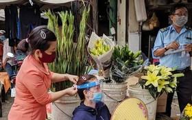 第五郡第十一坊婦女會主席 親自向商販戴上防護面罩。