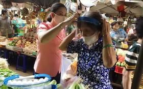 第十四坊婦女會主席向華人商販戴上防護面罩。