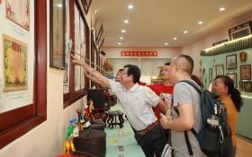 """作者的叔父在""""西堤華人懷舊物品展""""上向觀眾介紹我家昔日的""""全家福""""。"""