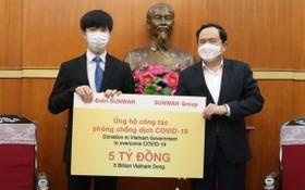 越南祖國陣線中央委員會主席陳清敏(右)接受新華集團捐贈50億元。