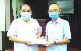 范興主任(右)轉贈本報讀者捐助的善款。