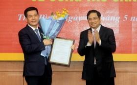 中央組織部長范明政(右)向阮鴻延同志頒授人事委任《決定》並送鮮花祝賀。(圖源:宣教部)