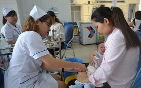 圖為一名護士在給寶寶打防疫針。(示意圖源:秋莊)