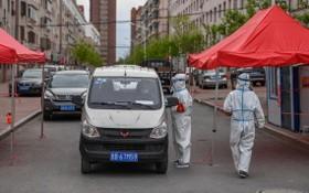 5月18日,在舒蘭市通機小區,工作人員為出入居民測溫登記。(圖源:新華社)