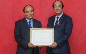 政府總理阮春福(左)向黨中央委員、政府辦公廳黨委書記、辦公廳主任梅志勇部長頒授40年黨齡紀念章。(圖源:光孝)