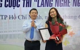 市人委會副主席楊英德向第一名得獎者頒發獎狀和祝賀鮮花。(圖源:黃潮)