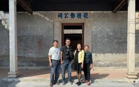 鄧越烽(左二)在故鄉的鄧公祠前與鄉親合影。