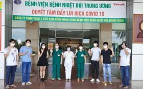 在中央熱帶病醫院收治的6名新冠肺炎患者痊愈出院前與醫護人員合照。(圖源:楊海)
