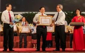 黨中央政治局委員阮文平(右二)向《勞動者報》總編輯蘇廷遵頒發獎狀。(圖源:吳絨)