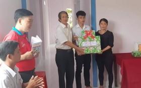 阮文菜老師在向阮陳日輝家庭贈送禮物分享入住新屋的喜悅。