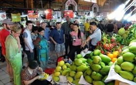 遊客參觀濱城市場的水果攤。(圖源:VNA)