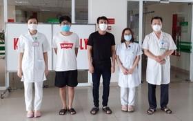 兩名新冠肺炎患者(左二、三)病癒出院前同醫護人員合照。(圖源:VOV)