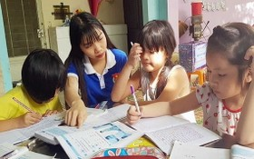 共青團團員給少兒輔導功課。(圖源:黎維)