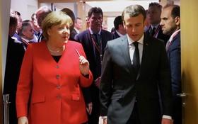 德國總理默克爾(左)與法國總統馬克龍交談。(圖源:新華社)