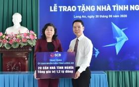 丁文成董事長(右)將善款轉交隆安省人委會代表。