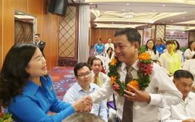 第五郡勞動聯團主席黎氏碧幸(左一)向模範勞工戴上花環祝賀。