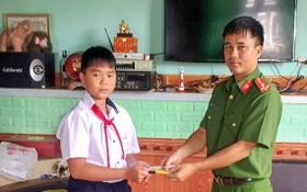 六年級學生高志源(左)將所拾到的款項轉交予當地公安派出所代表,以託尋找失主歸還。(圖源:慶福)