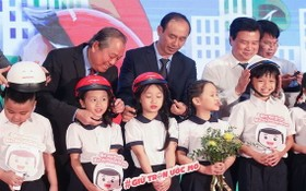"""張和平副總理(後左一)出席""""圓夢""""活動並親切為小學生扣上安全帽。(圖源:教育部)"""