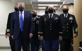 美國總統特朗普(左一)在訪問一家軍事醫療中心時,被拍攝到戴著口罩。(圖源:AP)