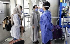 在伊朗德黑蘭的機場,工作人員為民眾量度體溫。(圖源:AP)