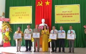 芹苴市越南祖國陣線委員會副主席阮翠姮(中)向華人同胞集體典範代表頒發獎狀。(圖源:芹苴電視台)