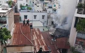 消防隊員爬上隔壁鐵皮屋頂展開滅火行動。(圖源:消防警察提供)