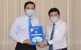 新任市工商廳長裴佐黃宇(左)從市人委會主席阮成鋒手中接過人事委任《決定》。(圖源:芳陲)