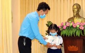市勞動聯團代表向家境貧困少兒贈送禮物。