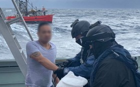 全副武裝的執法人員在浪高3.5米的惡劣環境下在海上突襲小船,逮捕了3人。(圖源:Getty Images)