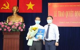 新任第五郡人委會副主席阮春忠(左)接領人事委任《決定》時與市人委會副主席楊英德合照。(圖源:梅花)
