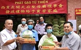 林和會長(左)與雙成隆安有限公司丁文森(右)向窮人贈送禮物。