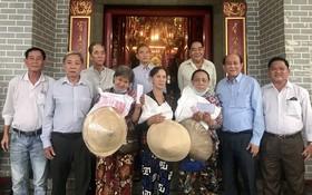 鄭鑫發(左二)、曾業文(右二)與值理會成員向窮人贈送禮物。