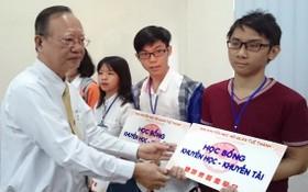 盧耀南理事長向廣肇大學生頒發獎學金。