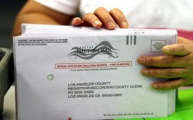 一名職員在辦公室對郵寄選票進行分類。(圖源:洛杉磯時報)