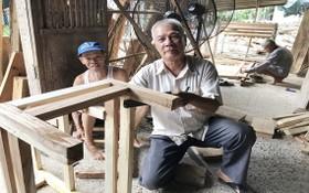 裴文盧(中)與慈善木匠組成員們在釘造凳子。