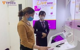 銀行職員正旨引客戶操作LiveBank 進行交易。