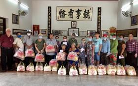 義安會館理事長陳裕(左一)向鄉親派發賑濟品。