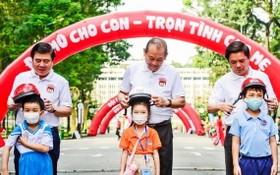 政府常務副總理張和平(中)和各位領導向小朋友們贈送安全帽。(圖源:元姮)