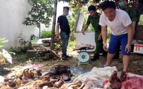 涉嫌違法者阮文成(白衣)及被宰殺的各種野生動物。(圖源:C.T.V)